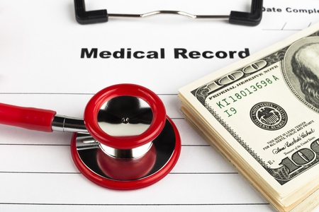 Money on a medical record clipboard with a red stethoscope isolated on white background photo