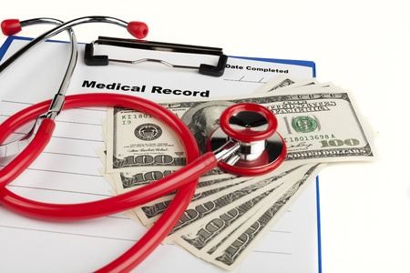 Money on a medical recor clipboard with a red stethoscope isolated on white background photo