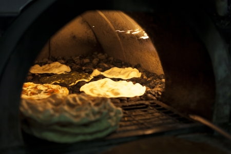 woodfired: Old style midle east stone oven with flat bread inside Stock Photo