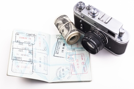 Open Israeli  passport full with visa with an old camera and dollars isolated on white background photo