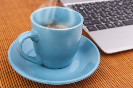 Morning coffee in a blue cup near a silver laptop on wood table with steam photo