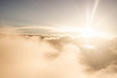 Zonsopgang boven de wolken tijdens een vlucht fel licht en kleuren