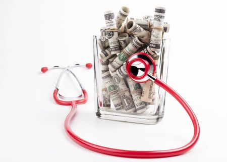 Health in a jar rolled dollars in ajar with a red stesthoscope isolated on white background photo