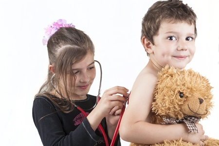 Two children playing doctor with a red stethoscope and a teddy bear isolated on white photo