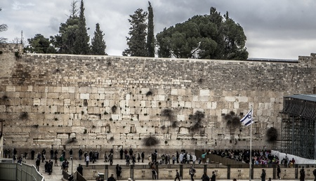 the wailing wall with people and cloudy sky