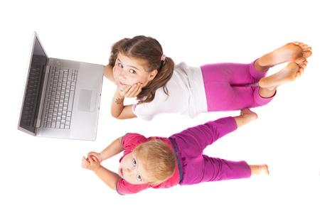 locking up: Two girls laying and locking up  with a silver laptop isolated on white