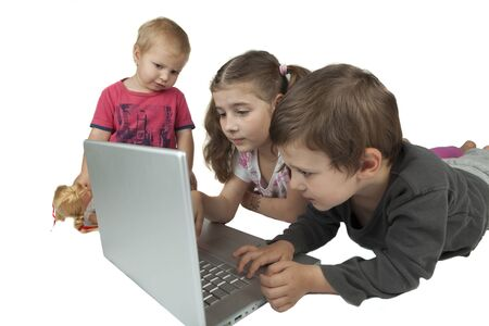 Children group two girls and one boy playing on a silver laptop isolated on white background photo