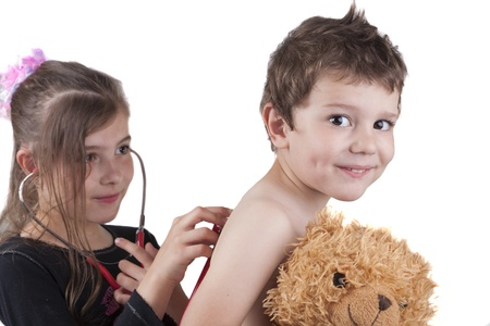 doctor toys: Girl and boy  playing doctor with a red stethoscope and a teddy bear isolated on white