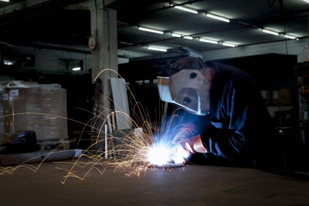 Heavy industry steel worker welding with sparks