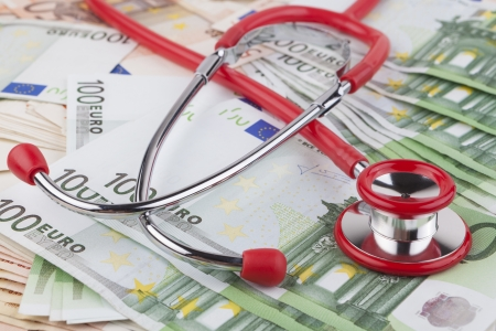 Red stethoscope on pile of euro banknotes  Stock Photo - 19627567