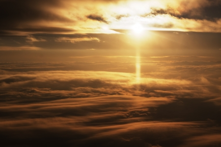 Bright sunlight at sunrise aerial view between two clouds