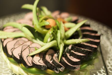 ornated: Sushi pile ornated with cucumbers and peppers on a plate