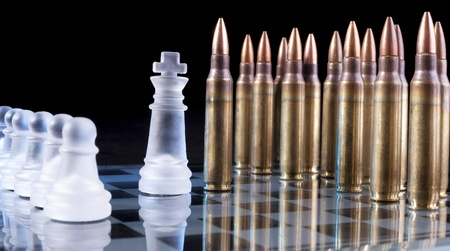 Battle field with bullets on glass chess table on black background with reflection photo