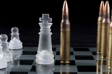 Machine gun bullets on glass chess board on black background photo