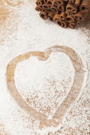 heart shape flour on brown wood cutting board photo