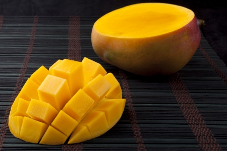 Mango slice cut to cubes close-up  on dark background photo