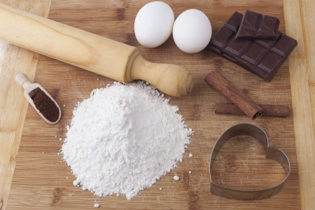 Baking ingredients and tools on brown wood cutting board photo