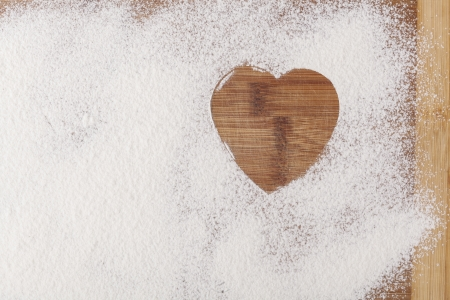 Heart shape flour on brown wood cutting board photo