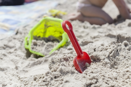 Red toy shovel in the sand with a green bucket in the background photo