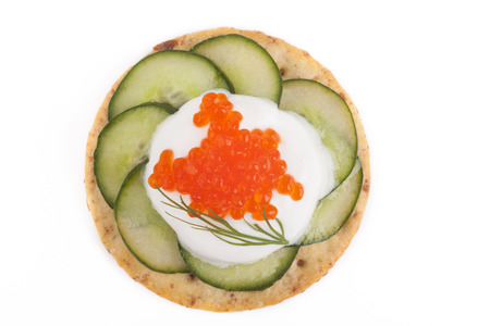 Red caviar on white chees and green cucumber apetiser on white background photo