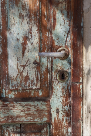 Old door handle on wooden blue textured door photo