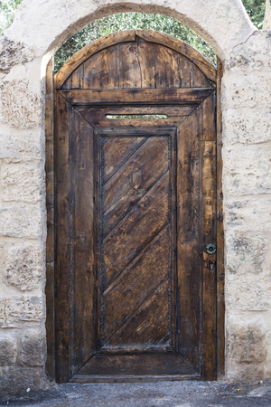 Old brown wood entrance door with white brick wall photo