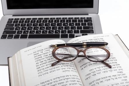 Old hebrew bible with glases a pen and silver laptop