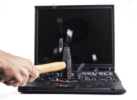 Barking black laptop with hammer flying keys isolated on white  photo
