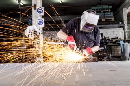 Worker Schleifen Metall in einem Workshop mit Funken fliegen