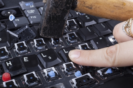 Woman finger on the hell keys of broken keyboard with hammer photo