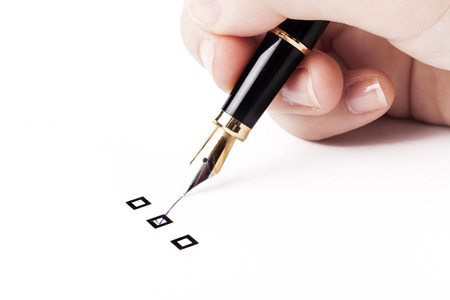 Female hand holding fountain pen and Marking  in middle check-box