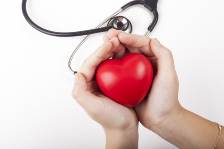 Holding red heart in two hands with black stethoscope in the background isolated on white photo