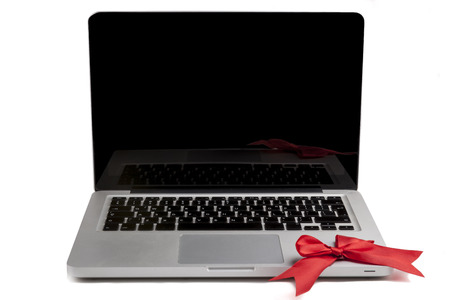 Silver Laptop with blank black screen and red bow on the keyboard isolated on white background photo