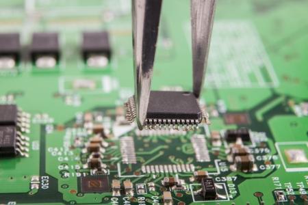 Montage: Montagemikrochip auf der gr�nen Elektronik-Platine mit einer Pinzette Lizenzfreie Bilder