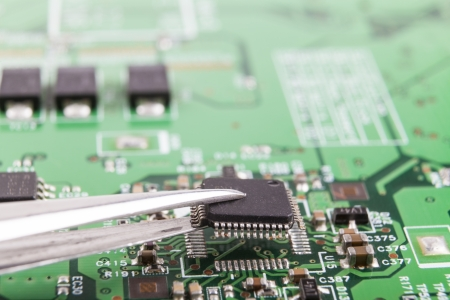 electronics industry: Mounting microchip on electronic circuit board with tweezers Stock Photo