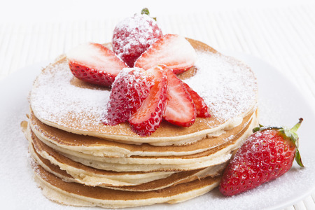 flapjacks: Pancakes on white background with  strawberry and sugar