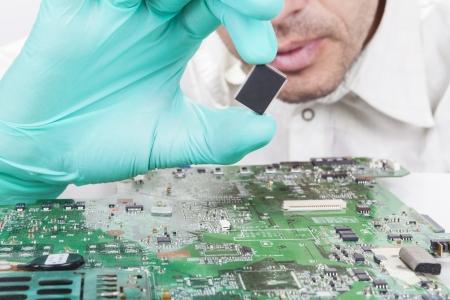 장갑과 전자 회로 기판에 마이크로 칩을 들고 스톡 콘텐츠
