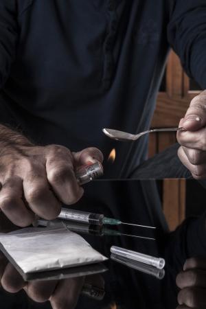 heroin: Preparing drugs on teaspoon a lighter on dark with reflection