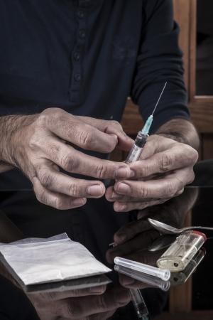 drogadiccion: Preparación de las drogas en una jeringa en la oscuridad con la reflexión Foto de archivo