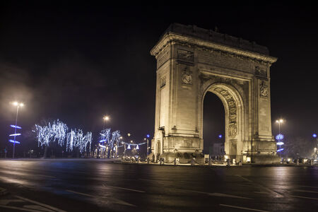 Arc de triomphe in a boulevard bucharest romania at night with lights photo