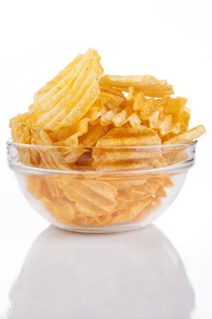 Glass bowl full with golden spicy potatoe chips on white background with reflection Stock Photo