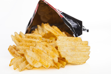 Golden poatato chips pouring out os a bag on white background