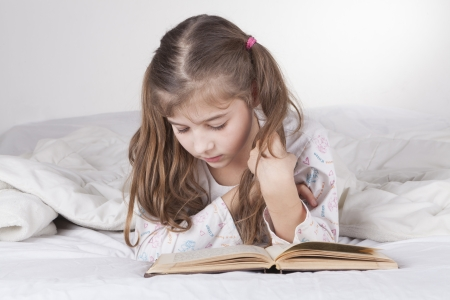 Little girl lying in bad and reading the bible written in Hebrew photo