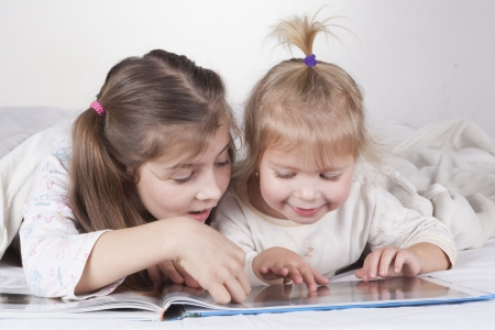 Two sisters reading bad time story in bad with white sheets photo