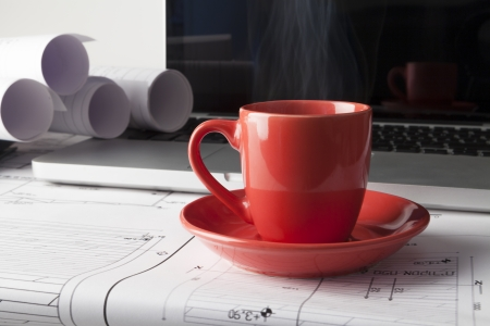 Architect drawing blueprints with a silver laptop with red cup of coffee photo