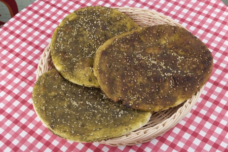 atar: Pita bread with zaatar green middle eastern herb on red table