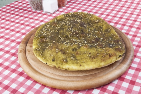 atar: Pita bread with zaatar green middle eastern herb on wood plate