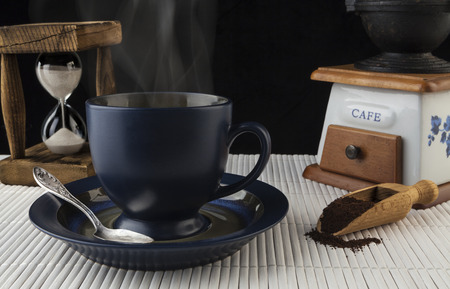 Blue steaming coffee mug with grinder and old wooden hourglass in the background photo