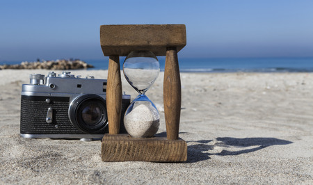 Old wooden hourglass and vintage camera on sand at sunny beach with blue sky photo