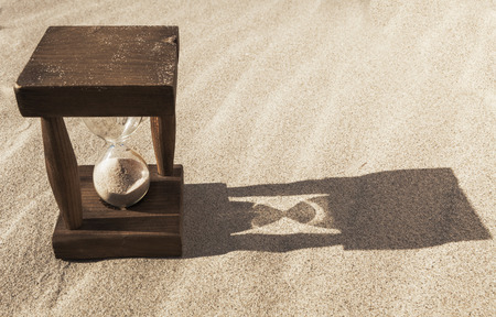 Old wooden hourglass in the sand with morning long shadow photo
